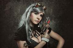 Steampunk woman with mechanical gun. Wall background stock photography