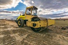 Steamroller выполнять выравнивающ работу на дороге под конструкцией стоковая фотография
