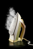 Steamy electric Iron reflected on black Stock Image