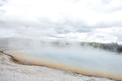 Steamy Shoreline. This was the shoreline of a very colorful and steamy hot spring at Yellowstone National Park. The steam and the clouds almost mesh together and Royalty Free Stock Photos