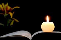 Stearinljus, öppnad bok och blommor som isoleras på svart Arkivbild