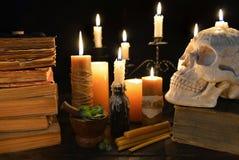 Stearinljus, böcker och mänsklig skalle på svart Arkivfoton
