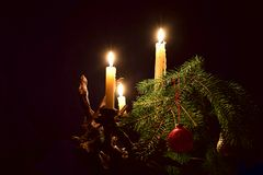 Stearinljus, en ljusstake och en julgran klippte med granen arkivbilder