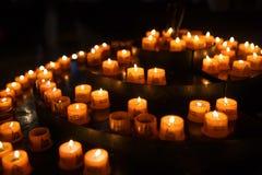 Stearinljus för böner i kyrka Arkivbild