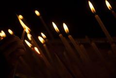 Stearinljus för kvinnahandbelysning i en kyrka, stearinljus och handen som sätter en ny stearinljus Sakrala bränningstearinljus i Royaltyfri Fotografi