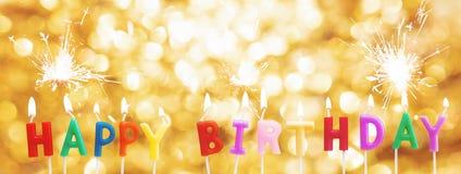 Stearinljus för lycklig födelsedag på guld- Bokeh tänder bakgrund med tomteblosset Arkivbilder