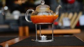 Stearinljus för te för havsBuckthorn som värma sig i japansk restaurang stock video