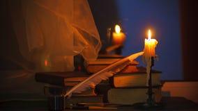 Stearinljus för Tid schackningsperiod och gamla böcker på nattetid Slapp fokus Filmiskt gradera för färg stock video