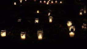 Stearinljus flammaljus på grav på all helgondag i kyrkogård på natten 4K arkivfilmer