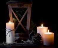 Stearinljus, grankotte och lykta på en svart bakgrund Royaltyfri Bild