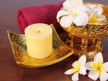 Stearinljus, handduk, färgvaror och tropiska blommor Royaltyfria Foton