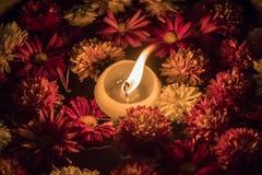 Stearinljus i en bunke mycket av blommor Royaltyfri Bild