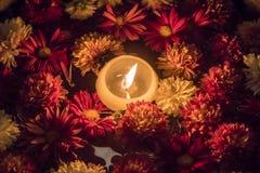 Stearinljus i en bunke mycket av blommor Arkivbilder