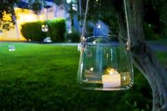Stearinljus i ett exponeringsglas som hänger från ett träd arkivfoton