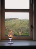 Stearinljus i ett fönster Royaltyfria Foton
