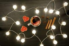 Stearinljus i formen av en hjärta, ett funderat vin med kryddor, en kanel och en anis Rottinglyktor på den svarta trätabellen, Arkivbild
