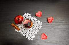 Stearinljus i formen av en hjärta, ett funderat vin med kryddor på en snöra åtservett, ett äpple och kanelbruna pinnar Arkivfoto