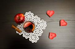 Stearinljus i formen av en hjärta, ett funderat vin med kryddor på en snöra åtservett, ett äpple och kanelbruna pinnar svart trä  Arkivfoton
