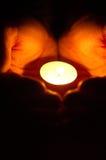 Stearinljus i händerna Fotografering för Bildbyråer
