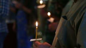 Stearinljus i händerna av troenden i den ryska ortodoxa kyrkan arkivfilmer