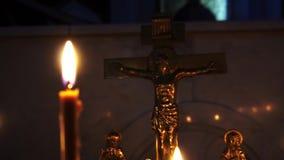 Stearinljus i kristen kyrka framme av korset långsam rörelse stock video