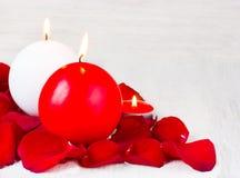 Stearinljus i kronbladen av röda rosor på en vit bakgrund, tomt utrymme för text Royaltyfri Foto