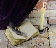 Stearinljus med den öppna boken Royaltyfri Foto