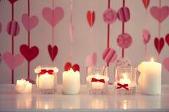 Stearinljus med röda hjärtor på bakgrund Arkivbild