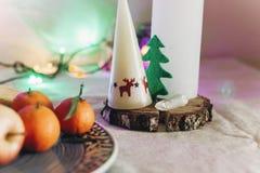 Stearinljus med ren- och julträdet på lantlig julflik Arkivbilder