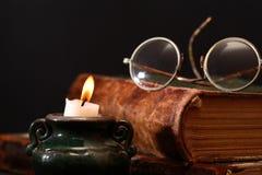 Stearinljus och bok Royaltyfria Bilder