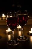 Stearinljus och ett exponeringsglas av vin returnerar afton Arkivfoton