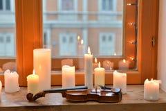 Stearinljus och fiol Arkivbild