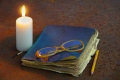 Stearinljus och gammal anteckningsbok som ligger på en gammal metall Arkivfoton
