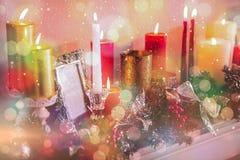 Stearinljus- och julgarneringar som är ordnade på spisen Arkivbilder