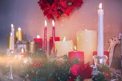 Stearinljus- och julgarneringar som är ordnade på spisen Arkivfoto