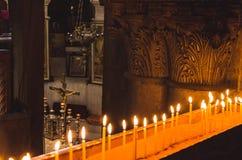 Stearinljus och kors i den Cathilic kyrkan Arkivbilder