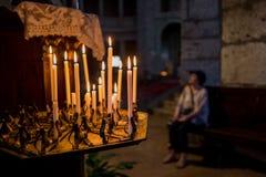 Stearinljus och kvinna i kyrka i helgonet Ambrogio Church i Milan Royaltyfria Foton