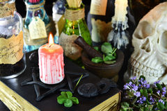Stearinljus på den svarta boken med cmagic objekt Royaltyfri Foto