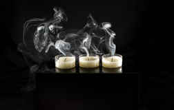 stearinljus släckte tre rök Arkivfoto