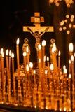 Stearinljus som bränner i den ortodoxa kyrkan, med ett kors i baksidan Arkivbild
