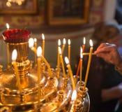 Stearinljus som bränner i ortodox kyrka arkivbilder