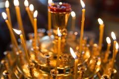 Stearinljus som bränner i ortodox kyrka arkivbild