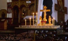 Stearinljus som bränner på en ljusstake som är främsta av guld- kors med J Arkivfoto