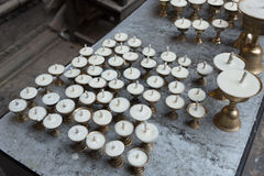 Stearinljus uppställda i rad i kloster i Nepal Arkivbilder