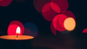 Stearinljuset bränner och vänder på en bokehbakgrund stock video
