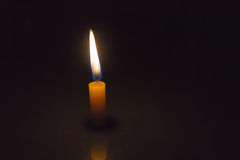 Stearinljuset för singeln tände enkelt i den mörka bakgrunden Royaltyfri Bild