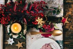 Stearinljuset tände på jultabellen som omgavs av festlig decorat Royaltyfri Foto