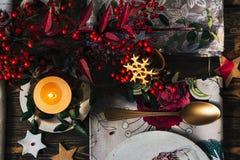 Stearinljuset tände på jultabellen som omgavs av festlig decorat Royaltyfria Foton