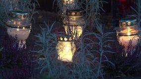 Stearinljusflamma på svartjordheden på grav i afton 4K stock video