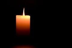 Stearinljusflamman tänds i mörkret royaltyfria bilder